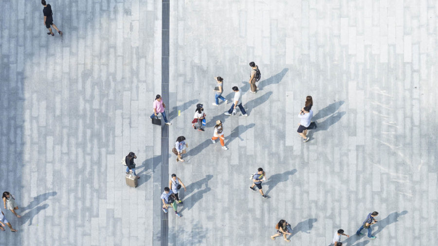 Bird's eye view picture of people walking on pavement