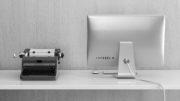 Black and white picture of typewriter next to Mac desktop illustrating digital transformation