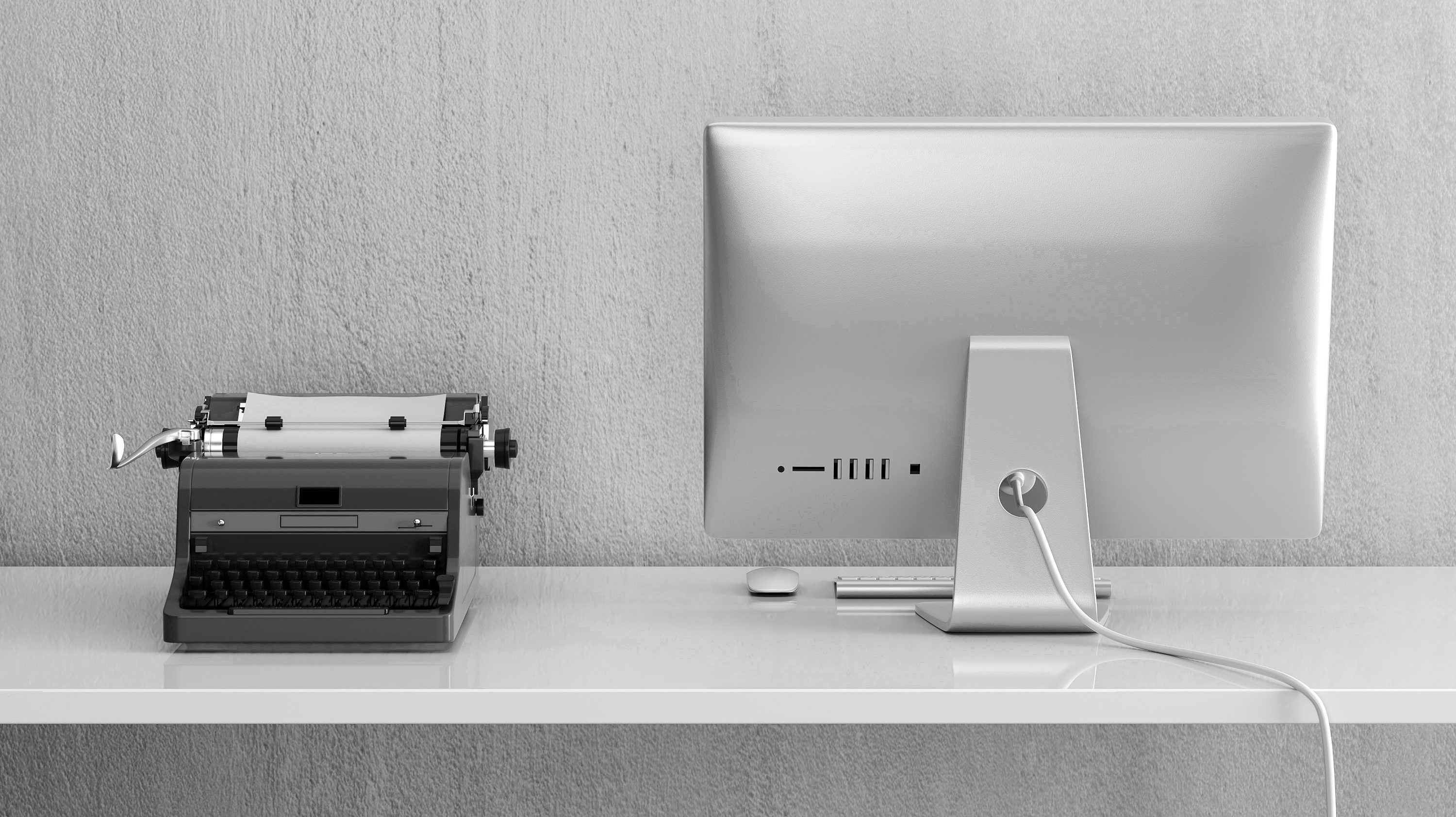Black and white picture of typewriter next to Mac desktop illustrating digital transformation