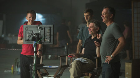 director and crew looking at screen behind scenes of filming