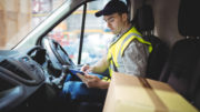 man from parcel delivery companies looking at tablet in truck