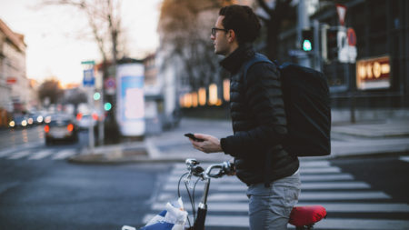 Man standing with bicycle holding phone