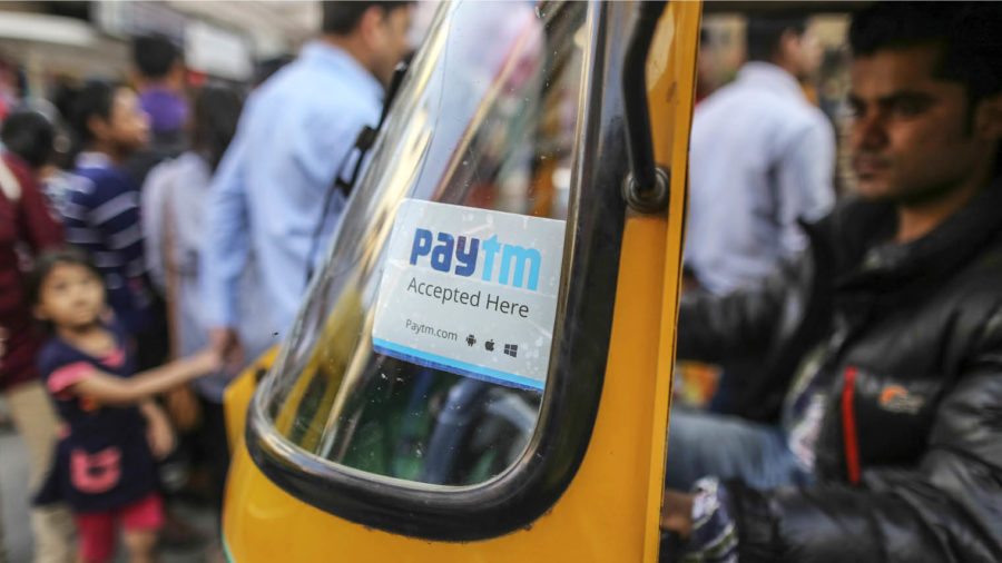sign for PayTM mobile payments system in window of Indian rickshaw