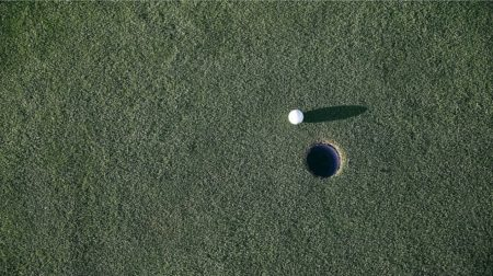 Golf ball almost in hole