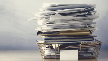 Stack of papers on desk representing workplace stress