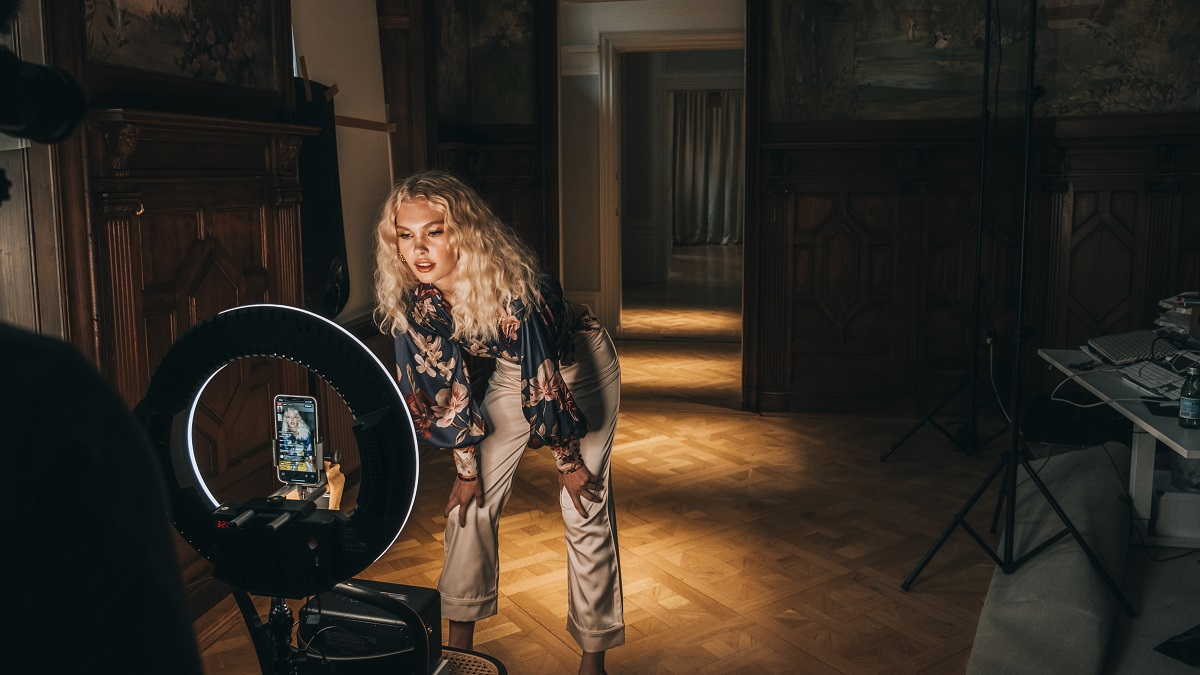 Model posing for live stream in front of a light ring