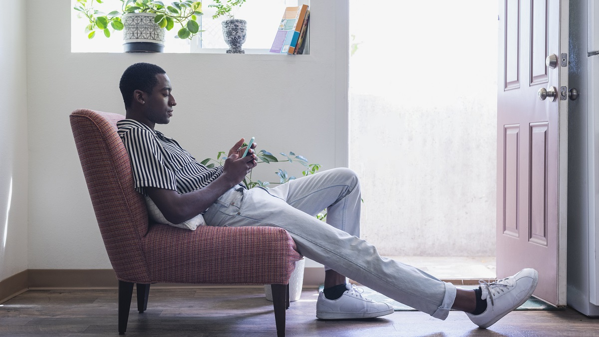 Young man sits in a chair looking at his phone