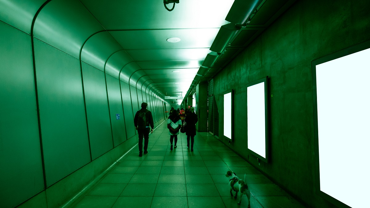 people and a dog walking through a green subway tunnel with glowing billboards