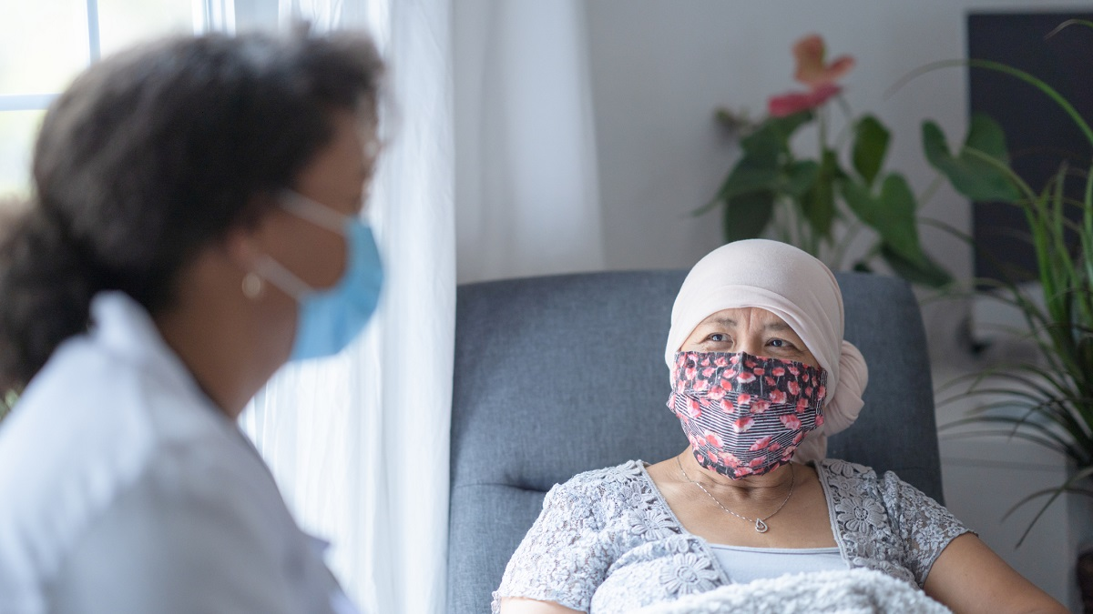 In a hospital room, an asian female cancer patient is chatting with her doctor. Both of them are wearing a mask during the coronavirus pandemic to help prevent the transfer of germs. The doctor is a female and of African American ethnicity.