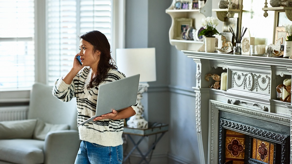 Woman talking on the phone to someone while holding a laptop
