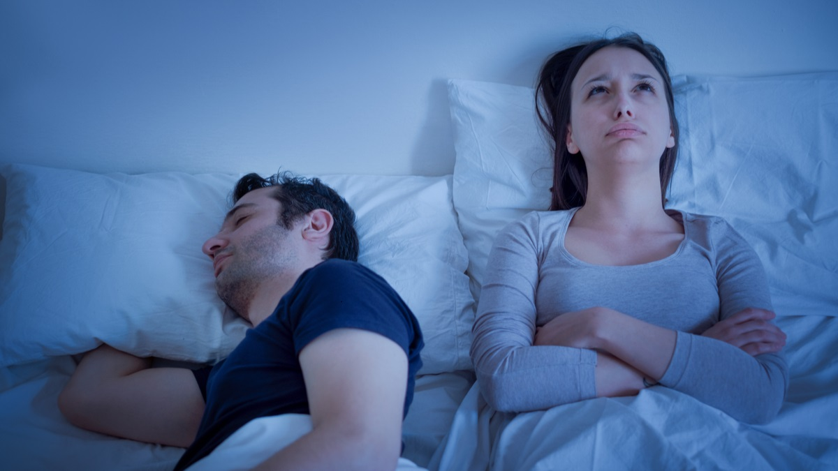 Woman lying awake next to a man who is asleep