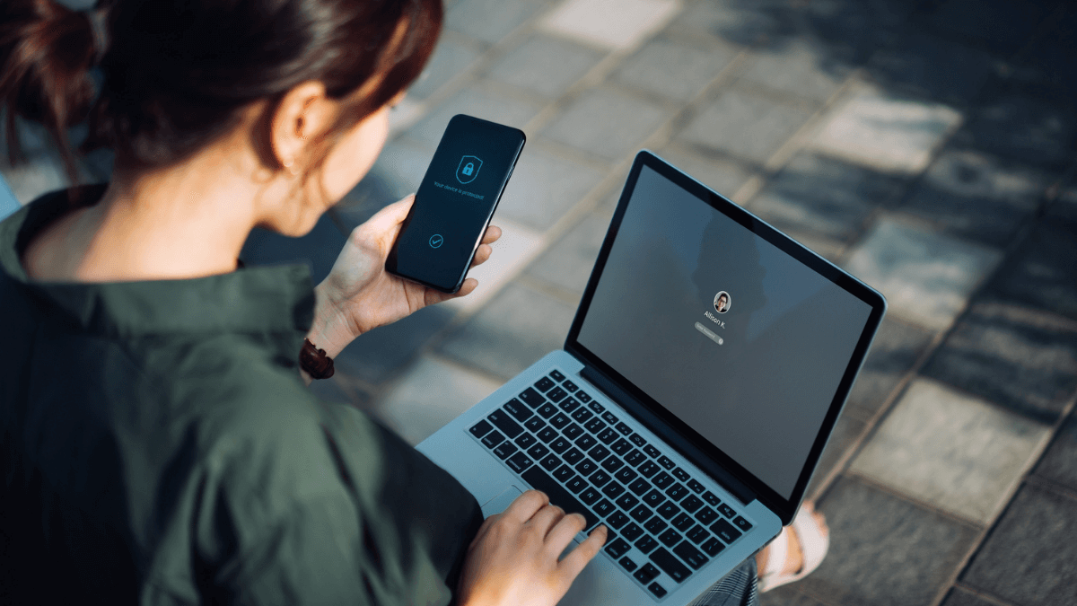 Woman logging into laptop through two-factor authentication