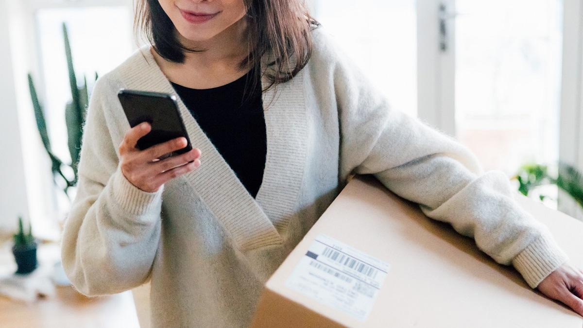 Woman looking at phone holding box