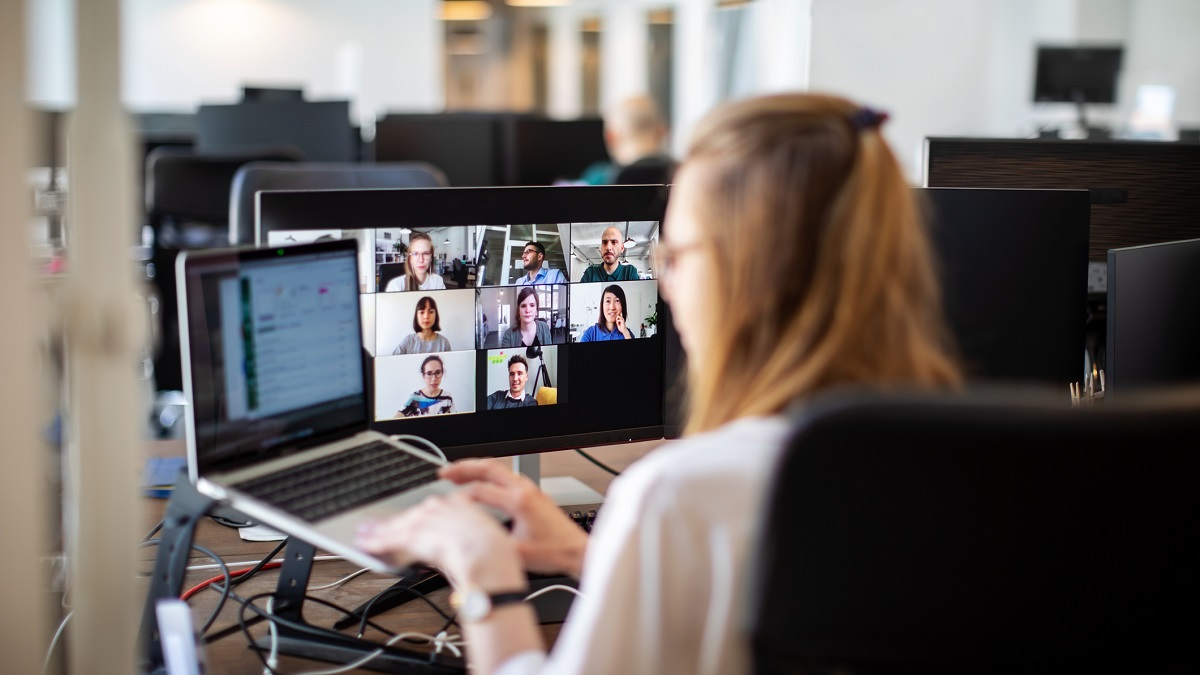 Woman in an office, on a video call with collegues