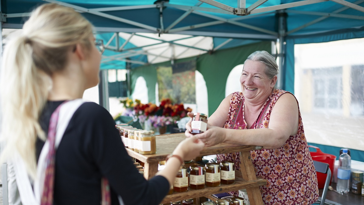 A senior woman working on a local market stall selling homemade jam serves a customer.