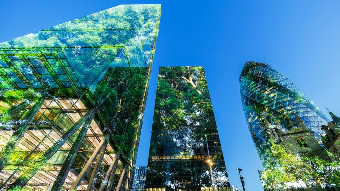 Buildings in the City of London with trees reflected in them, against a blue sky