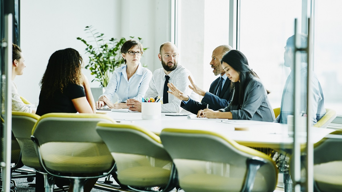 Mature businessman leading meeting in office conference room