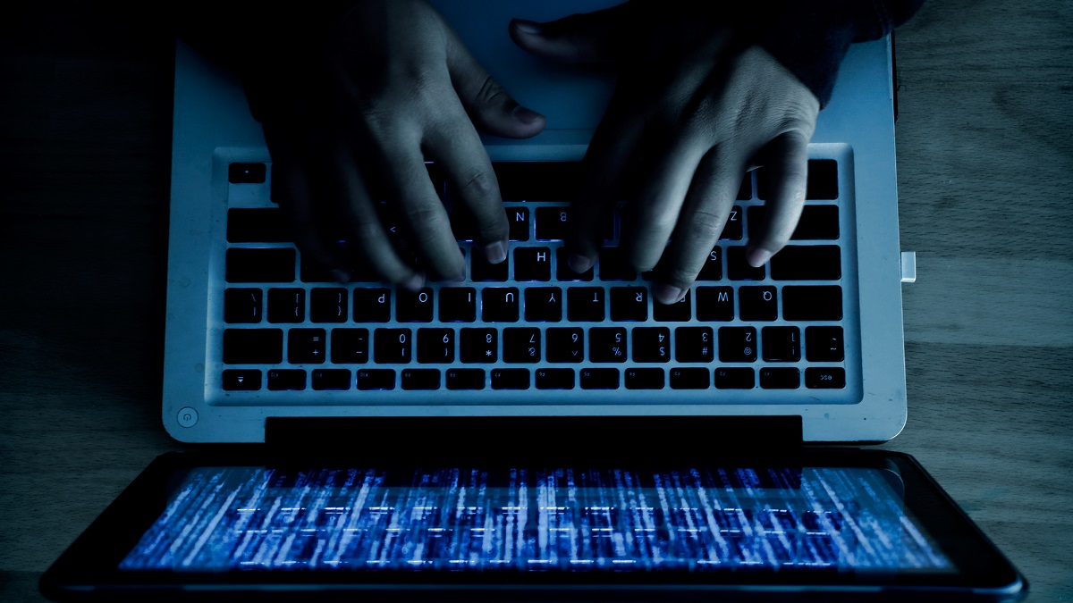 A computer programmer or hacker prints a code on a laptop keyboard to break into a secret organization system. Internet crime concept.