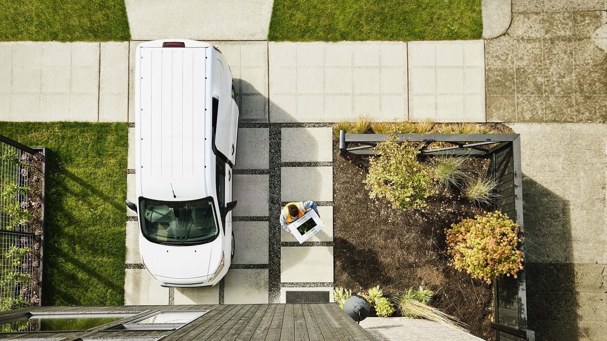 Overhead view of female delivery driver carrying produce box to front door of home