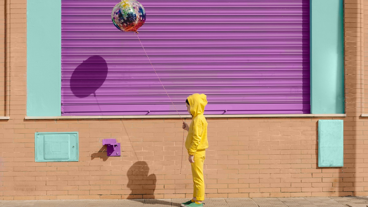Little girl dressed in yellow with balloon