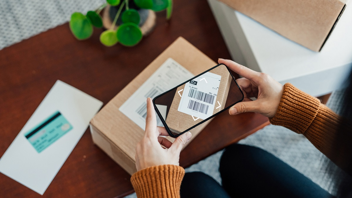 Woman Scanning Delivery Barcode On Package With Smart Phone