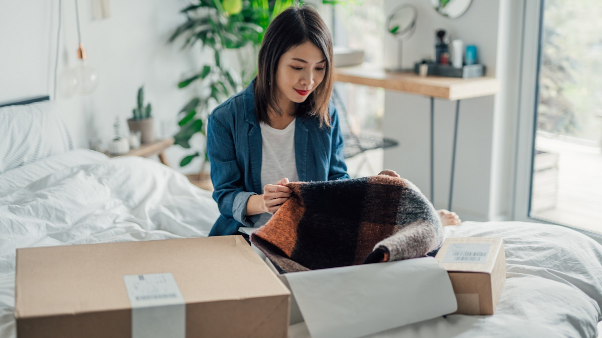 Beautiful smiling young Asian woman unpacking delivery box. Online hopping at home is efficient and convenience. Home Delivery service.
