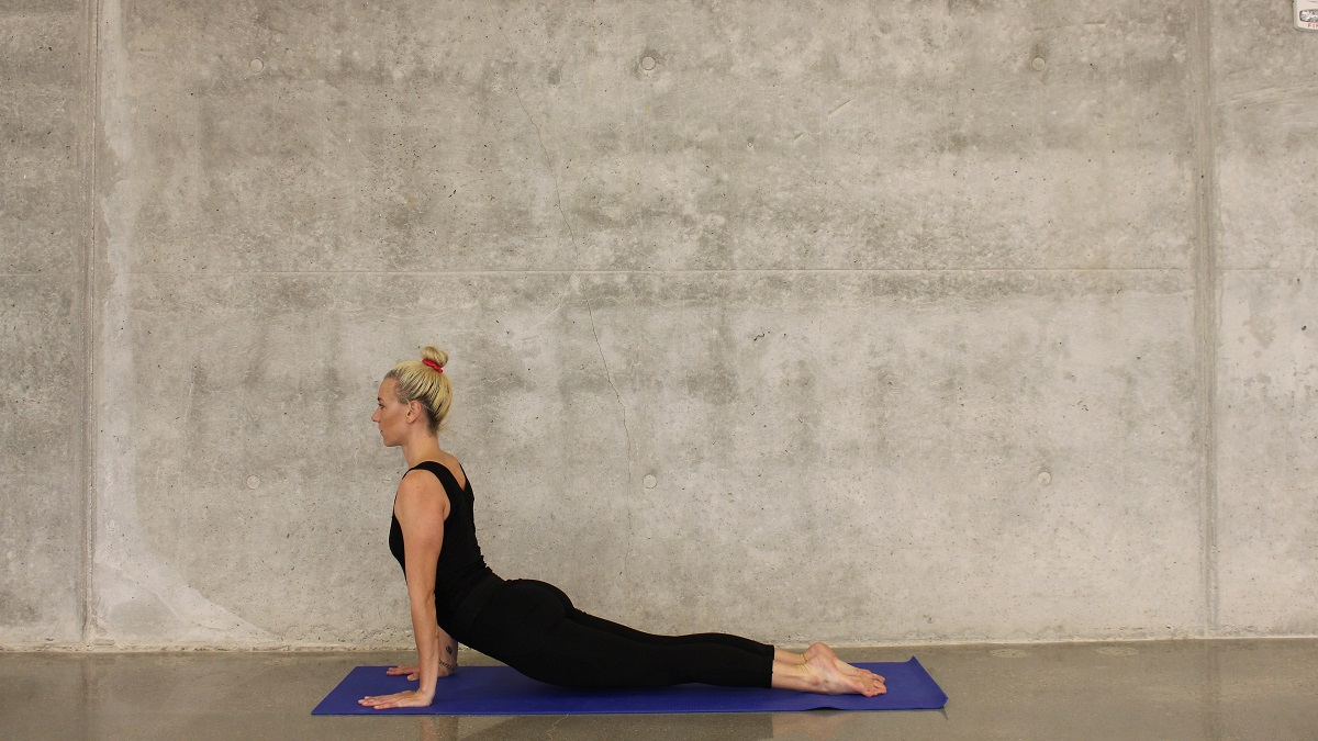 Woman in yoga pose against concrete wall