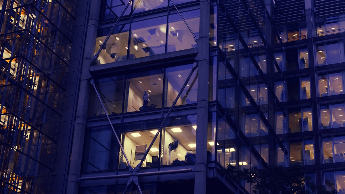 The windows of an office building at night with the silhouette of a person working late. City of London