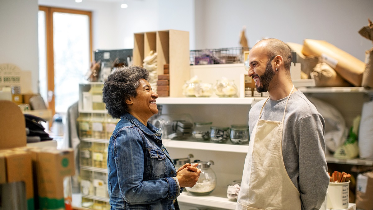 Smiling owner and customer laughing at illuminated zero waste store