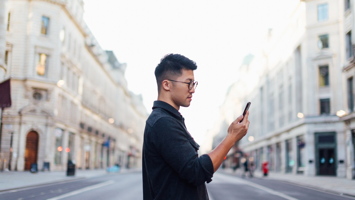 Confident Man Exploring The City With Smartphone